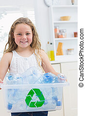 Smiling girl carrying box of the bottles