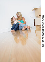 Smiling mother and daughter sitting on floor