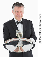 Smiling waiter serving glass of wine on tray - Smiling...