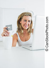 Smiling woman using laptop to shop online