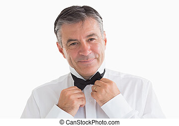 Well-dressed man adjusting his bow tie - Well-dressed and...