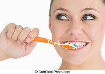 Cute woman washing her teeth in the white background