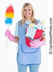 Cleaning woman holding feather duster with a bucket in the...