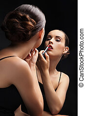Beautiful young woman near mirror with lipstick - Beautiful...