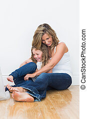 Mother tickling her daughter - Laughing mother tickling her...