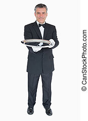 Waiter holding out empty silver tray - Smiling waiter...