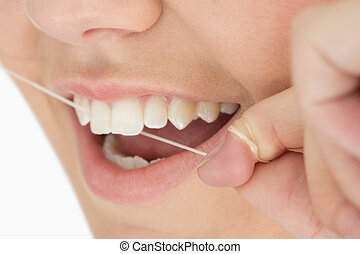 Close up of mouth and dental floss in the white background