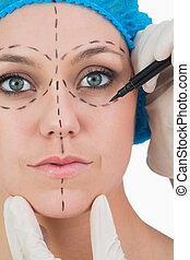 Doctor drawing on woman's face for face lift on white...