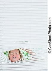 Girl peeking out of blinds - Smiling girl peeking out of...