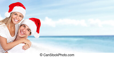 Happy christmas santa couple on the beach Holidays