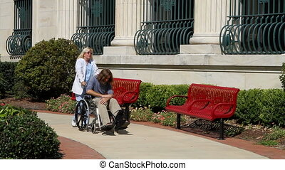 Nurse Pushing Wheelchair - Nurse pushes a depressed mental...