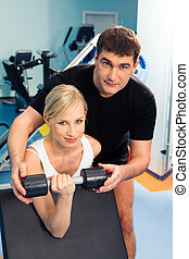 In the sport club - Blonde woman lifting weight with man...