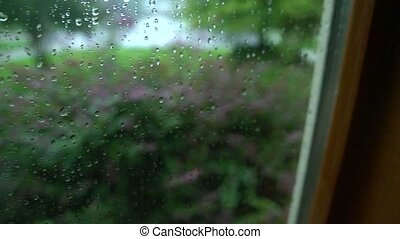rainy window pan - Pan across a rain-soaked window looking...