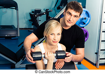 Health club - Image of trainer assisting young woman in the...