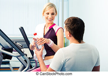 During sport training - Image of man giving the bottle of...
