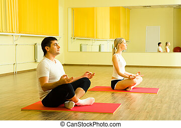 Meditation - Photo of young man and woman sitting together...
