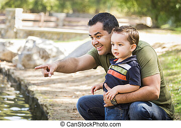 Hispanic Father Points with Mixed Race Son at the Park -...
