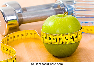 Apple diet - Photo of fresh green apple tied with measuring...