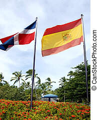 Flag of the Dominican Republic against the blue sky, flowers...