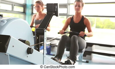Two women drawing on row machine