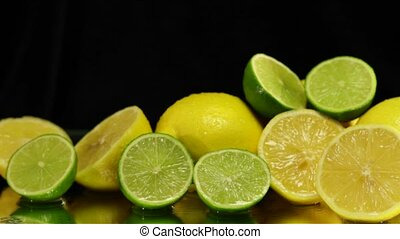 Wet Lemons and Limes on Black - Pile of fresh Juicy water...