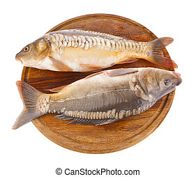 fresh fish (carp) on wooden board isolated white background