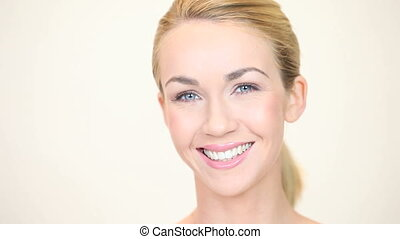 Blonde woman smiling facing forward