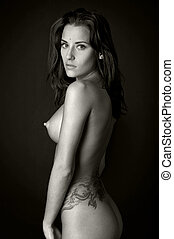 Back of the beautiful naked woman with tattoo. Photo with...