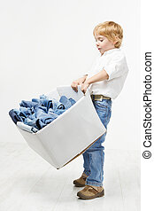 Child carrying cardboard box packed with jeans. Kids...