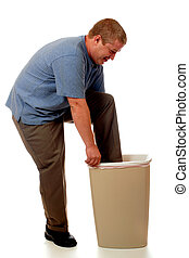 Human Trash Compactor - A man using his foot to compact the...