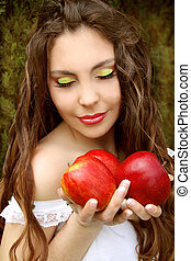 Portrait of Pretty young woman with three red apples.