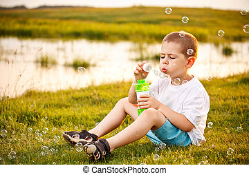 Boy blowing bubbles in the park