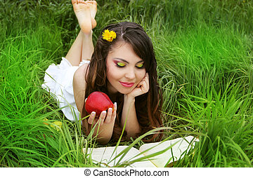Smiling Young Woman with red Apple reading the book in the Orchard. Green grass