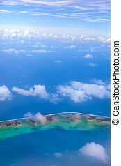 The atoll ring in ocean is visible through clouds. Aerial view.