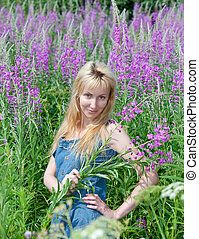 The smiling young woman with bunch of willowherb flower