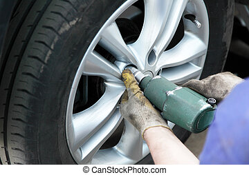 removing the tire of a car to replace the