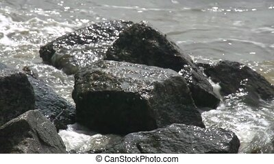 waves on rocks slow mo - Tight shot of waves crashing onto...