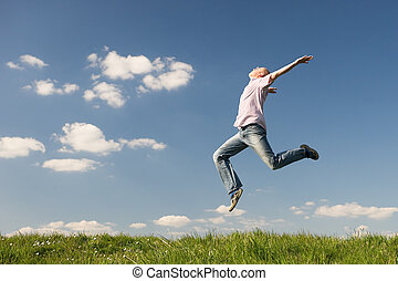 Feel happy - Young man is jumping over a green Use it for...