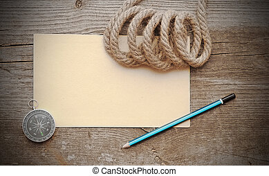 old paper, compass and rope on a old wooden background