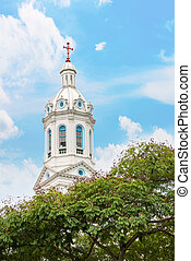 White church spire with trees and cloudy blue sky.Church of...