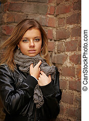 Beautiful girl in autumn coat standing near red brick wall....