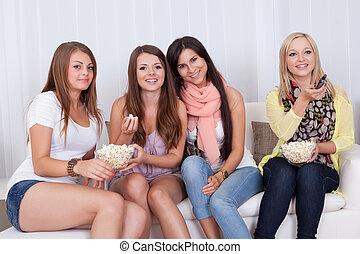 Four beautiful women watching TV