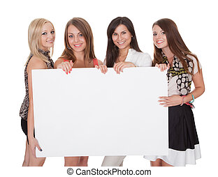 Four attractive women with blank sign - Four attractive...