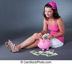 Woman saving 100 euro notes in a piggybank - Attractive...