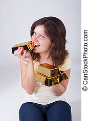 Woman eating gold bars - Young woman holding and eating gold...