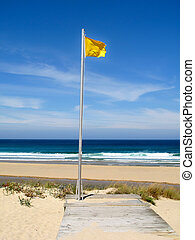 Attention, yellow flag on the beach