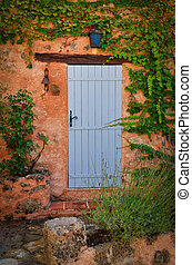Old blue door in orange wall - Old blue entrance door in...