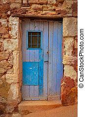 Old textured door in a stone wall
