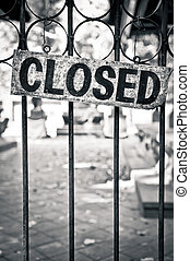 Monochrome closed sign on metal bars of the gate
