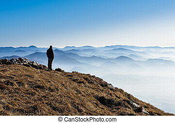 Silhouette of a man above misty mountains, blue sky,...